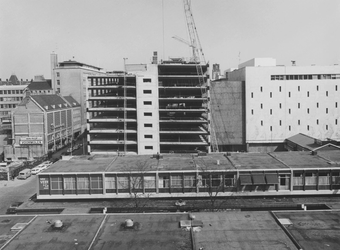 1974-1224 De bouw van de parkeergarage van magazijn De Bijenkorf (rechts) aan de Hennekijnstraat. Op de voorgrond ...
