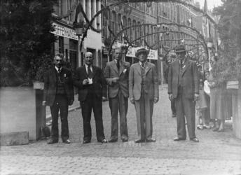 1974-1690 Leiders van het feestcomité staan voor de versierde Helmersstraat, hoek van de Kruisstraat. Op de foto (van ...
