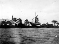 1975-183 De Schaardijk (Kralingseveer) met rechts oliemolen de Liefde, gezien vanaf de Nieuwe Maas.