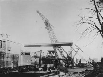 1975-60 Transport waterleiding aan de Honingerdijk. Drijvende bok tilt een waterleidingbuis. Op de voorgrond sleepboot ...