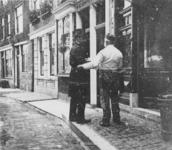 1977-18 De heer J.C. Teekens, zeilmaker, in het gesprek voor zijn huis aan de westzijde van de Aelbrechtskolk. Op ...