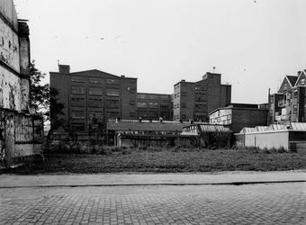 1977-1883 De noordzijde van de voormalige fabriek van Jamin in de Hugo de Grootstraat. Linkerzijde nog bewoonde woningen.