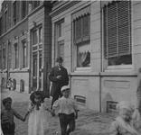 1977-210 De oostzijde van de Havenstraat. De heer L. Busemeijer staat voor een paar wandelende kinderen.