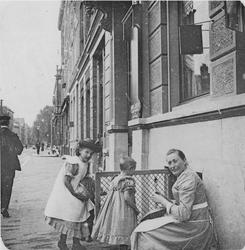 1977-25 Dienstbode Kaatje en twee meisjes voor het huis van notaris mr. A. van Mens, nr. 146.