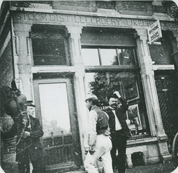 1977-30 Drie mannen voor de slijterij aan westzijde van de Havenstraat 11. Op de gevel: Stoomdistilleerdery en Likeurstokery.