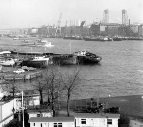 1977-314 Gezicht op de Nieuwe Maas, de Maaskade op het Noordereiland met rechts het Hulstkampgebouw en op de ...