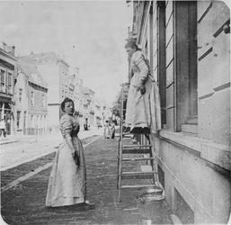 1977-34 Dames: duivenbode en dienstbode Maria voor het huis van notaris A. van Mens nr. 146, aan de oostzijde van de ...