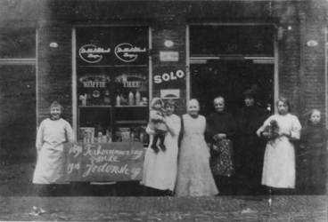 1980-1900 Kruidenier mevrouw E. Kerkhof-Bos en personeel voor haar winkel aan de Jodensteeg.Op het bord links staat: ...