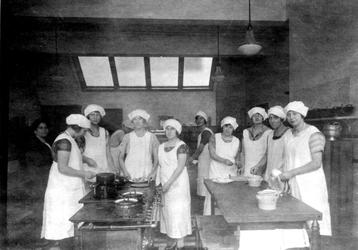 1980-4016 Interieur Rotterdamse Huishoudschool aan de Graaf Florisstraat nummers 45-61. Leerlingen in de keuken.
