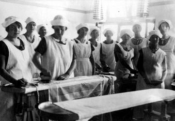 1980-4017 Interieur Rotterdamse Huishoudschool aan de Graaf Florisstraat nummers 45-61. Leerlingen in het strijklokaal.