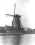 1986-656 Gezicht op de Delfshavense Schie en de Hoekmolen met open molenkap aan de Spangesekade. De Hoekmolen is in ...