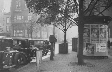 IX-1353-7 Het Van Hogendorpsplein met rechts een reclamezuil beplakt met affiches.