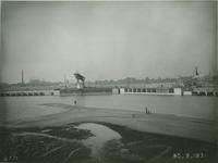 VII-371-01 Merwehaven tijdens de bouw van de kademuur langs de oostelijke oever. Op de achtergrond Schiedam.