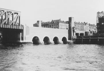 X-49-02-1 De vleugelmuren van de Willemsbrug, aan de zijde van de Maaskade op het Noordereiland. Rechts de hefbrug over ...