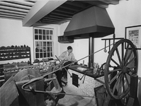 XII-105-09-3 Werkplaats in het zakkendragershuisje aan de Voorstraat. Op de achtergrond H. van den Berg (tinnegieter) ...