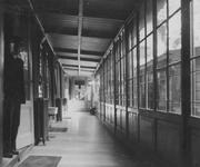 XII-90-00-01-17 Werknemer bij een gang in het gebouw van de Gemeentelijke Geneeskundige- en Gezondheidsdienst ( G.G. en ...