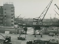 XIV-239-06 Lekhaven met loodsen en hijskranen op het terreinen van de Handelskamer. Op de achtergrond links het gebouw ...