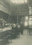 XXI-86 Leeszaal van de Gemeentebibliotheek aan de Boijmansstraat met de ambtenaren: zittend links F.J. Hoogeveen, ...