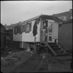 2760 Kinderen in de deuropening van hun noodwoning aan de Kleiweg ter hoogte van de Diamantweg. Onder de woning zit een ...