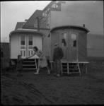 2762 Twee noodwoningen aan de Kleiweg van dichtbij met de bewoners, een oudere man, en een jonge vrouw met haar ...