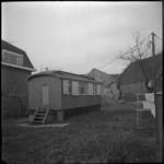 2763 Een noodwoning aan de Kleiweg tussen de Diamantweg en de Scherpendrechtseweg. Op de achtergrond zijn veel ...