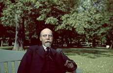 163 Vakantiefoto van Richard Boske sr. op een bank in een park.