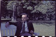 164 Vakantiefoto van Richard Boske jr. op een bank in een park.