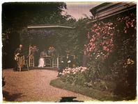 2 Twee mannen en vrouw in tuin.