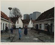 1367 Mensen lopen door het verlaten Witte Dorp. Uit een serie over de sloop van het Witte Dorp voordat het wordt gesloopt.