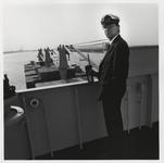 1988-1409 Rijksloods van de Regionale Loodsencorporatie Rotterdam-Rijnmond op de brug van een containerschip dat op de ...