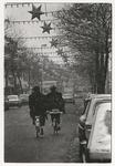 1989-4746 Twee fietsers in de Zwart Janstraat, Noorderboulevard. De straat is versierd met kerstverlichting. Uit een ...