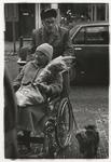 1989-4747 Ouder echtpaar, waarvan de vrouw in een rolstoel zit, in de Zwart Janstraat. Uit een serie van 10 ...