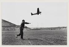 5 Man op klompen gooit zijn modelvliegtuig in de lucht. Uit eens serie van 8 foto's over recreatie op de Maasvlakte.