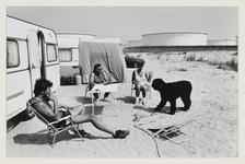 6 Drie mensen en een hond kamperen met caravans vlakbij opslagtanks. Uit eens serie van 8 foto's over recreatie op de ...