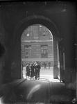 2002-1642 Een huwelijksplechtigheid op het stadhuis.Het gezelschap gezien door een poort van het stadhuis.