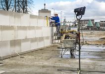 GS-92 Bouwvakker stapelt een muur op de bouwplaats van 'Hof aan de Hef'met op de achtergrond de Koninginnebrug op de ...