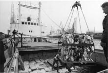 1968-1699 Het inladen van pakken kleding in het ruim van het Noorse motorschip Felto uit Haugesund, voor verscheping ...