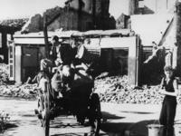 1968-262 Bewoners van de gebombardeerde binnenstad voeren met een paard en wagen hun huisraad weg.