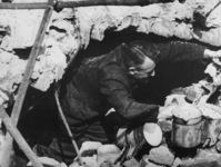 1968-263 Een slachtoffer van het Duitse bombardement van 14 mei 1940 zoekt naar huisraad tussen de restanten van zijn huis.