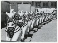 1970-2628 Een rij kermispaardjes op wielen staat klaar bij de Hugo de Grootstraat op het terrein van de voormalige ...