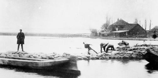 1975-565 Bezoek van autoriteiten aan de dijkdoorbraak in de Noordkethelpolder te Schiedam. Leggen van zandzakken op de ...