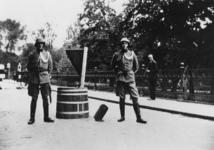 1976-1856 Twee Nederlandse soldaten bewaken de plaats waar een niet ontplofte bom uit het wegdek steekt van de Plantageweg.