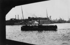 1979-2277 Een bootje varend op de Nieuwe Maas is afgeladen met arbeiders. Op de achtergrond het verwoeste ...