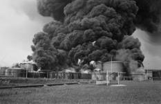1979-2278 Grote zwarte rookwolken stijgen op na een bombardement op een olieopslagplaats bij de 1e Petroleumhaven.