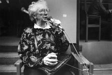 1989-318 Een oudere vrouw spreekt via een microfoon de anderen toe in het gebouw Odeon ter gelegenheid van ...