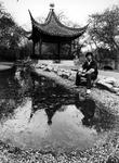 1990-545 Een Chinese man poseert in Diergaarde Blijdorp bij een Chinees tuinhuisje dat door zusterstad Shanghai aan ...