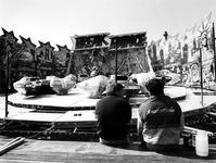 1990-636 Twee kermisexploitanten rusten uit bij het opbouwen van hun attractie op de Rivoli-kermis.