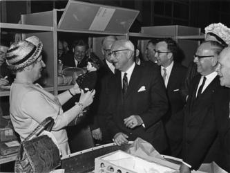 XXXIII-1345 Op de voorgrond H.M. Koningin Juliana die een PTT-pop ontvangt gedurende haar werkbezoek aan het PTT ...