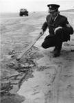 XXXIII-1703 Politieagent bij aangespoelde olie op het strand van Hoek van Holland.