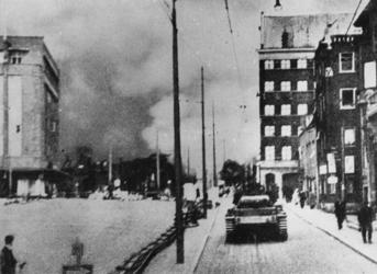 XXXIII-566-09-3 Duitse militairen op een tank komen aan in de brandende binnenstad. Links het warenhuis Gerzon gezien ...